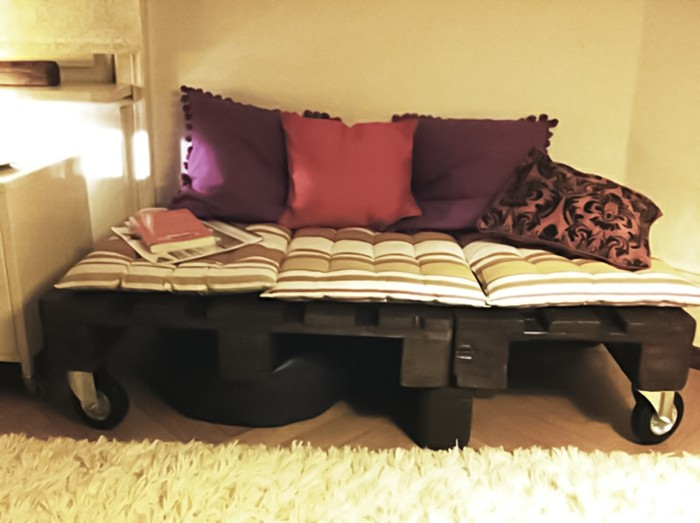 two purple cushions, a fuchsia pink cushion, a pink and black patterned cushion, and three striped white and beige pillows, decorating a black pallet sofa