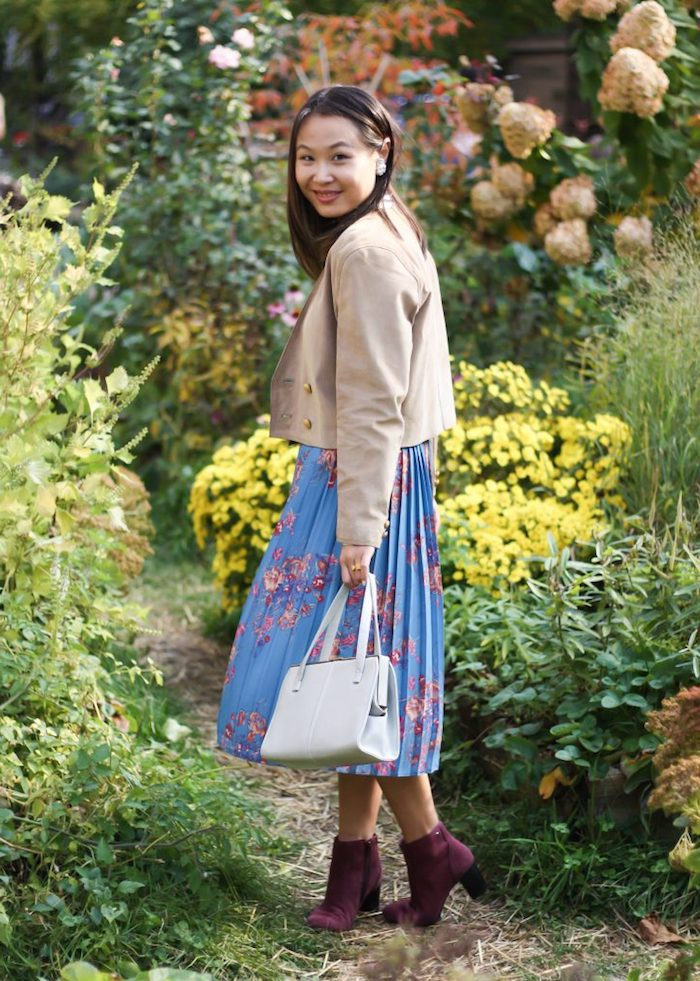 smiling brunette girl, wearing a blue pleated skirt, with pink floral pattern, purple ankle boots, and a beige jacket, garden party attire, white leather hand bag