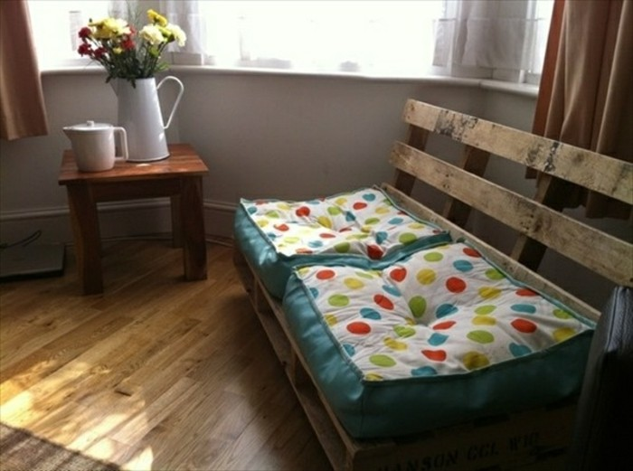 diy pallet settee, with two square pillows, in white and turquoise, with multicolored polkadots, small wooden table with a jug of flowers, and a teapot nearby