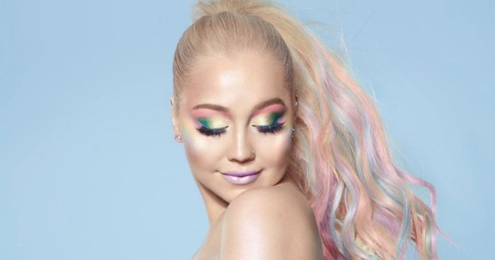 smiling young woman, with platinum blonde hair, featuring strands of pastel blue, pink and purple, tied in a ponytail, wearing unicorn makeup, with green and yellow eyeshadow