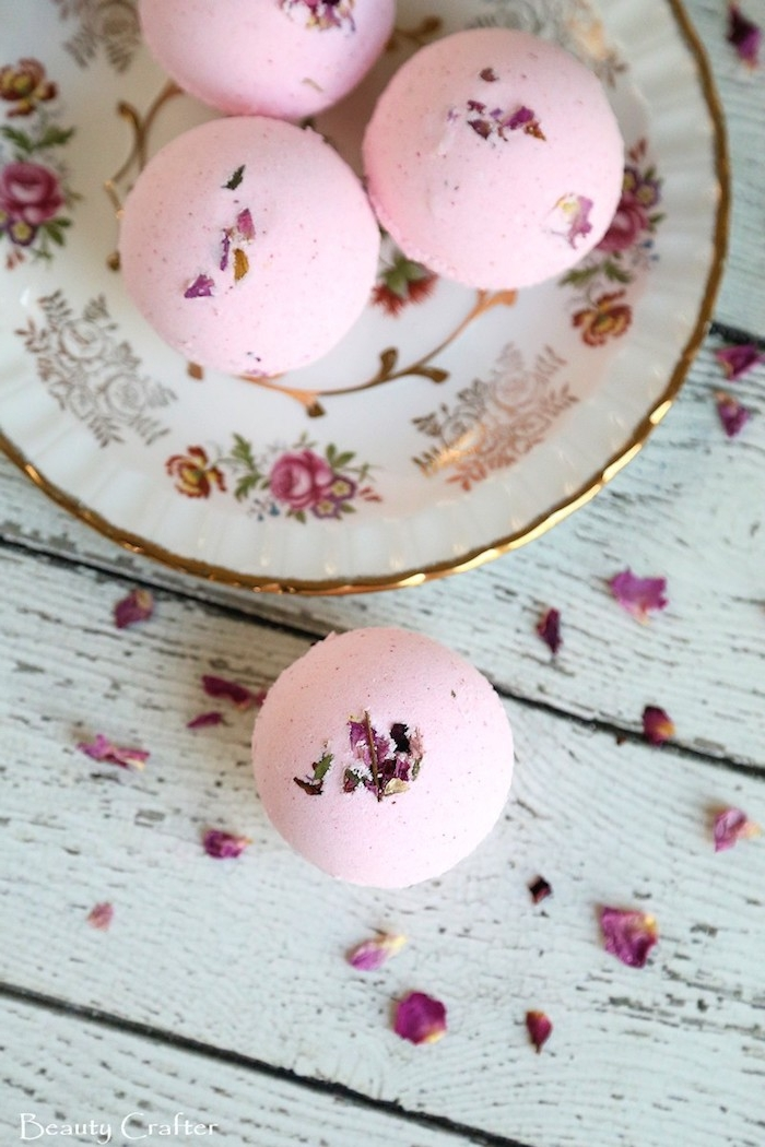 ornamental porcelain plate, with floral motifs and gold rim, containing three pink bath bombs, what is a bath bomb, another bath bomb, and dried rose petals outside of the plate