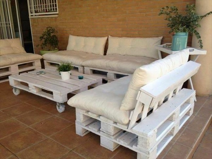a set of three white sofas, made from pallets covered in pillows, and a matching white pallet table on wheels, how to make pallet furniture, placed on a porch