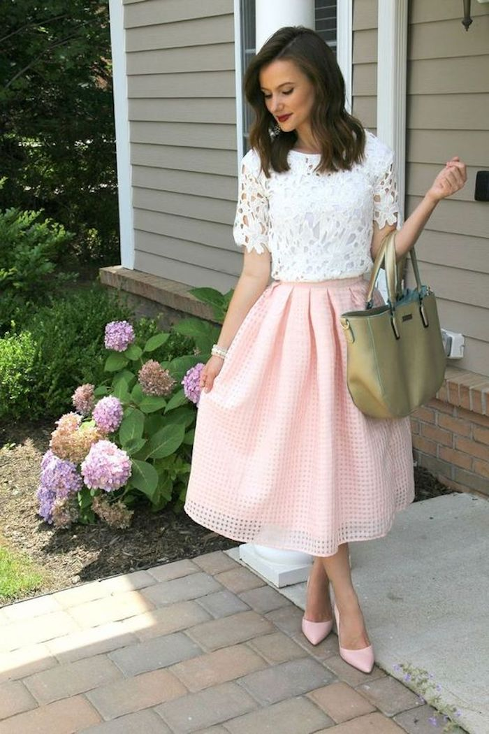 what is semi formal attire, skirt in a textured pale pink fabric, flared and medium long, worn with a white lace top, pink high heels, and a khaki bag, brunette woman with red lipstick