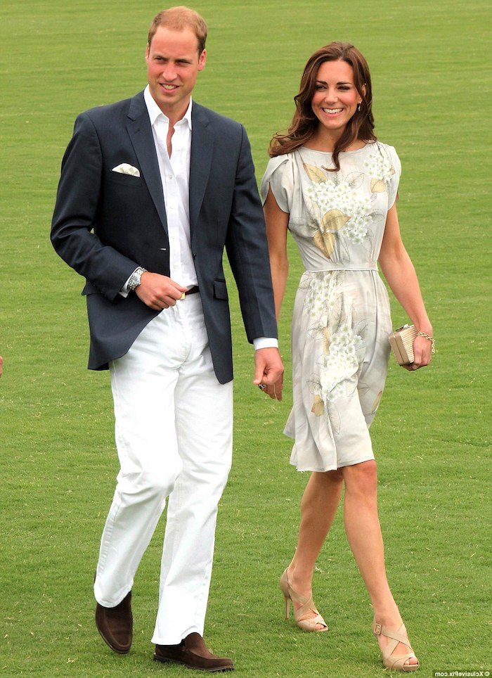 kate middleton and prince william, walking on a green field, dressed in garden party attire, pale beige knee-length dress, with pale floral pattern, white trousers and shirt, with black blazer
