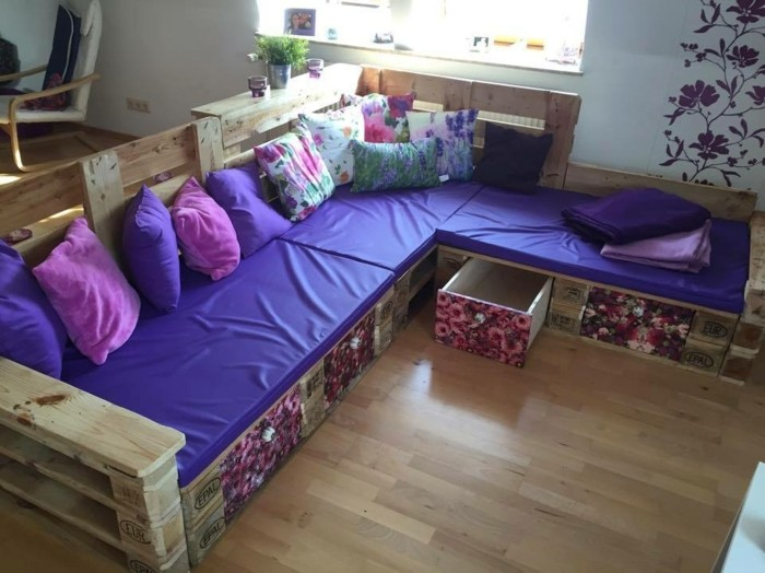 violet and purple covers and pillows, on top of a diy sofa, made from wooden pallets, with storage spaces, several multicolored cushions