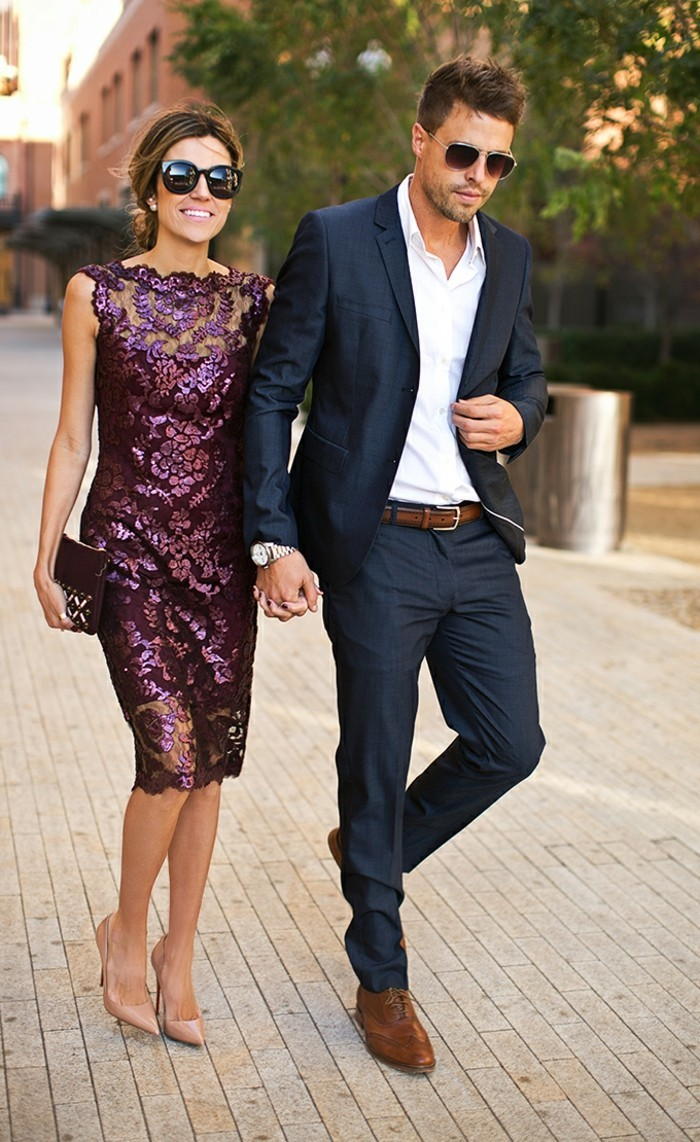 mens summer wedding attire, dark blue suit, worn with white shirt, and brown leather shoes and belt, by man walking hand in hand with woman, in purple lace dress