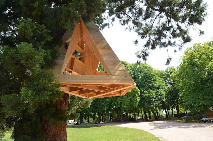 shelter made from pale wooden material, shaped like a pyramid, diy treehouse, hanging from a large fir tree, in a park