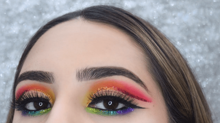 sparkly multicolored rainbow eyeshadow, worn with black eyeliner, makeup ideas, on brown-eyed young woman, with smooth brunette hair