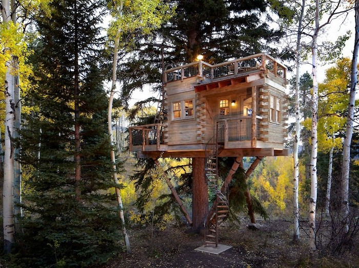 winding staircase leading to a backyard treehouse, built on several large trees, wooden structure with two terraces