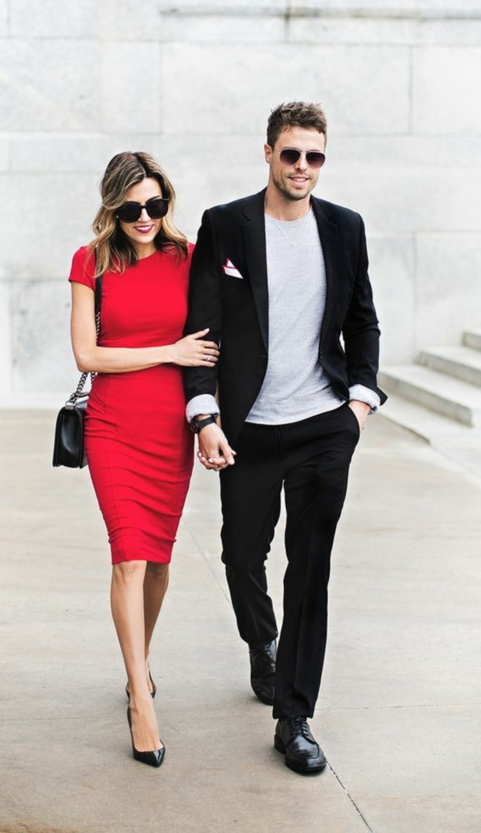 mens casual summer wedding attire, black suit and an off-white t-shirt, on young man with sunglasses, walking with a blonde woman, in a red midi dress