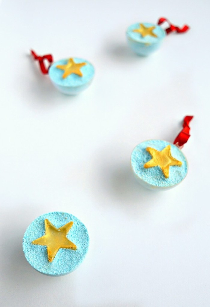 us flag inspired bath bombs, light blue and tied with red ribbons, each decorated with a yellow star, shaped like half spheres