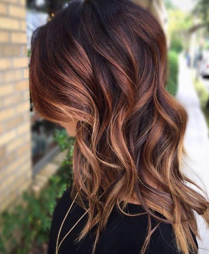 mid length dark auburn hair, with light streaks, styled in loose curls, dark brown hair with blonde highlights, worn by woman in black top