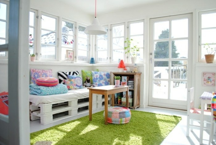 diy sofa made from white pallets, and decorated with multicolored cushions, inside a bright room, with several windows and a glass door