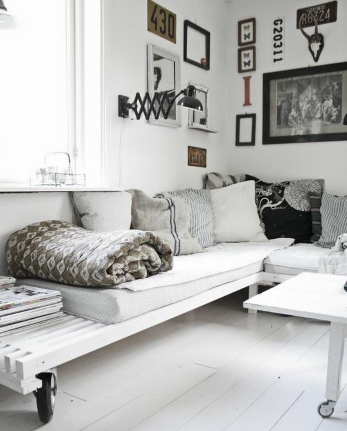 nordic style room, with white wooden floor, white walls with many framed images, and white furniture made from pallets