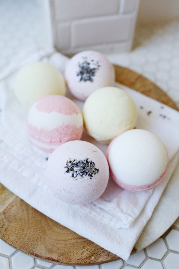 wooden board covered with white napkin, containing six bath bombs, in pale yellow, striped pink and white, and pale pink with lavender sprinkles, how to use a bath bomb