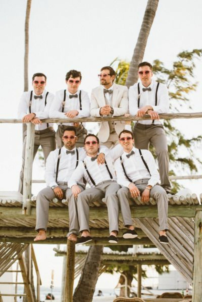 groom in white suit, surrounded by six barefoot men, wearing matching clothes, mens wedding guest attire, white shirts and beige trousers, with suspenders and bowties