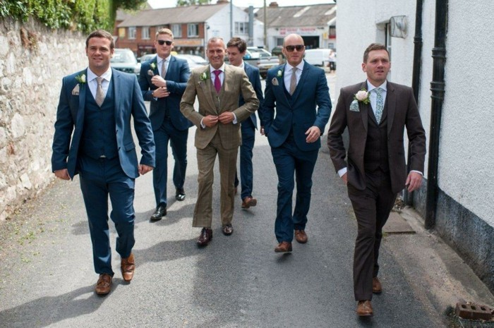 group of men in dark blue, and beige suits, with ties in different colors and boutonnieres, how to dress for a wedding male, walking down the street