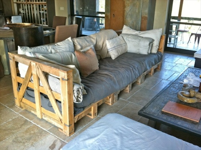 country style diy pallet sofa, covered with grey textile, and a multitude of pillows, in different sizes, coffee table nearby