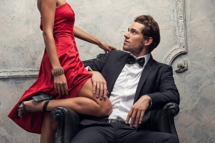 shiny red dress, and black sandals, worn by slim woman, leaning against a sitting young man, in a black suit, with a white shirt, and a black bowtie