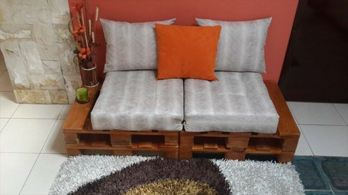 small settee for two people, made from pallets painted brown, covered in striped grey pillows, and decorated with a small orange cushion, pallet couch