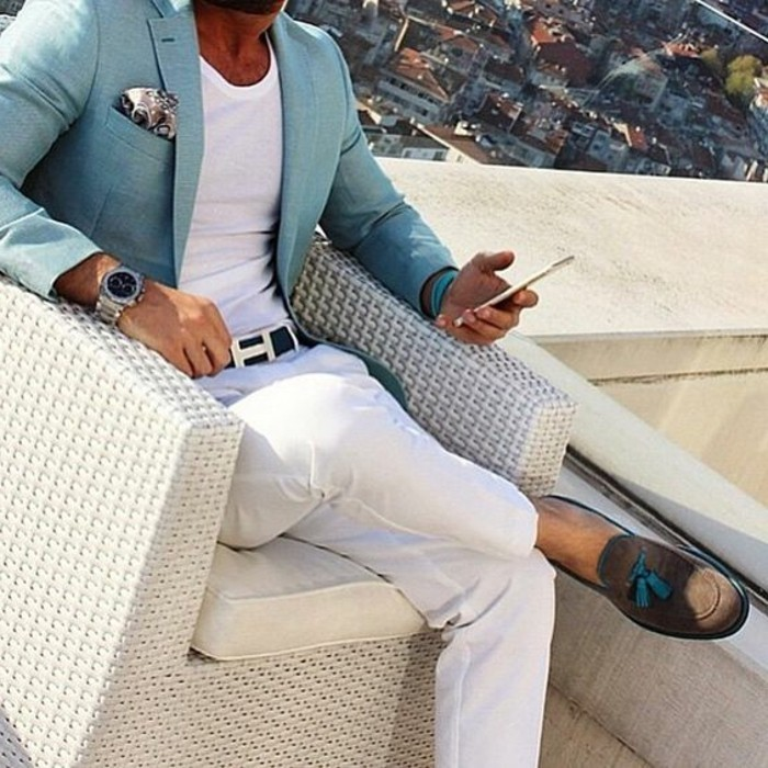 light turquoise blazer, with patterned pocket handkerchief, worn by man sitting in a chair, mens casual summer wedding attire, with white t-shirt, white trousers and beige suede loafers