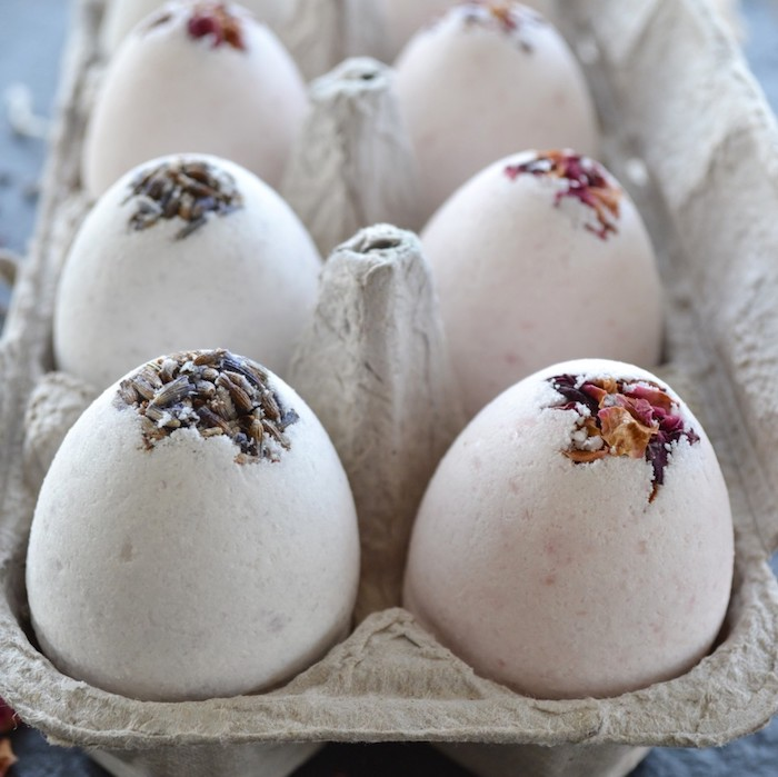 dried lavender and rose petals, on top of six or more, very pale blue and pale pink bath bombs, bath bomb recipe, gray cardboard egg box