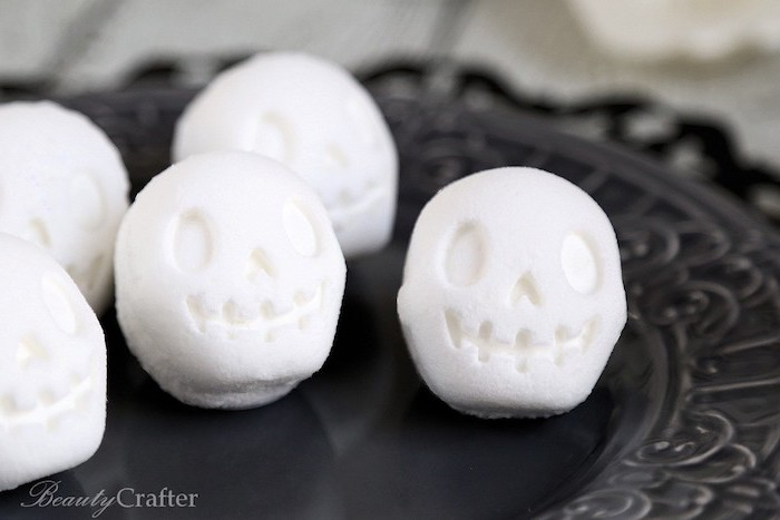 decorative black plate, containing several white bath bombs, shaped like smiling cartoon skulls