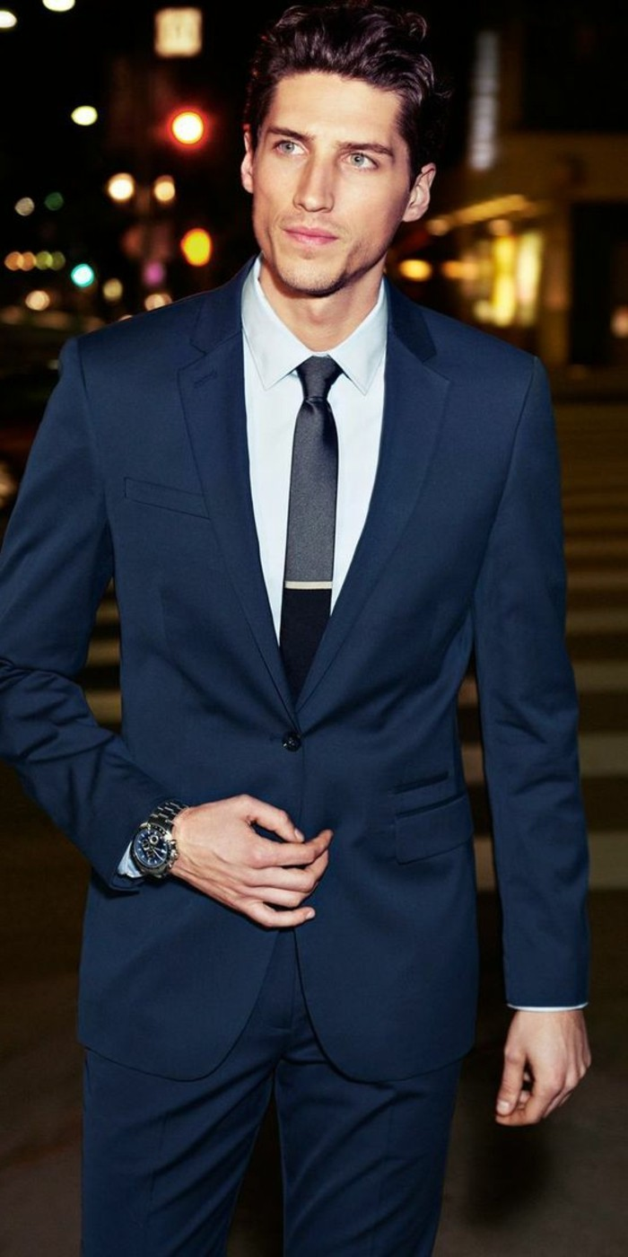 young man wearing a dark blue, two piece suit, with white shirt, and a shiny black tie, with a silver pin, black tie attire for men, a street at night