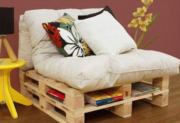 armchair made of wooden pallets, with storage space, furniture made from pallets, covered with large, soft pale beige pillows, and decorated with three cushions