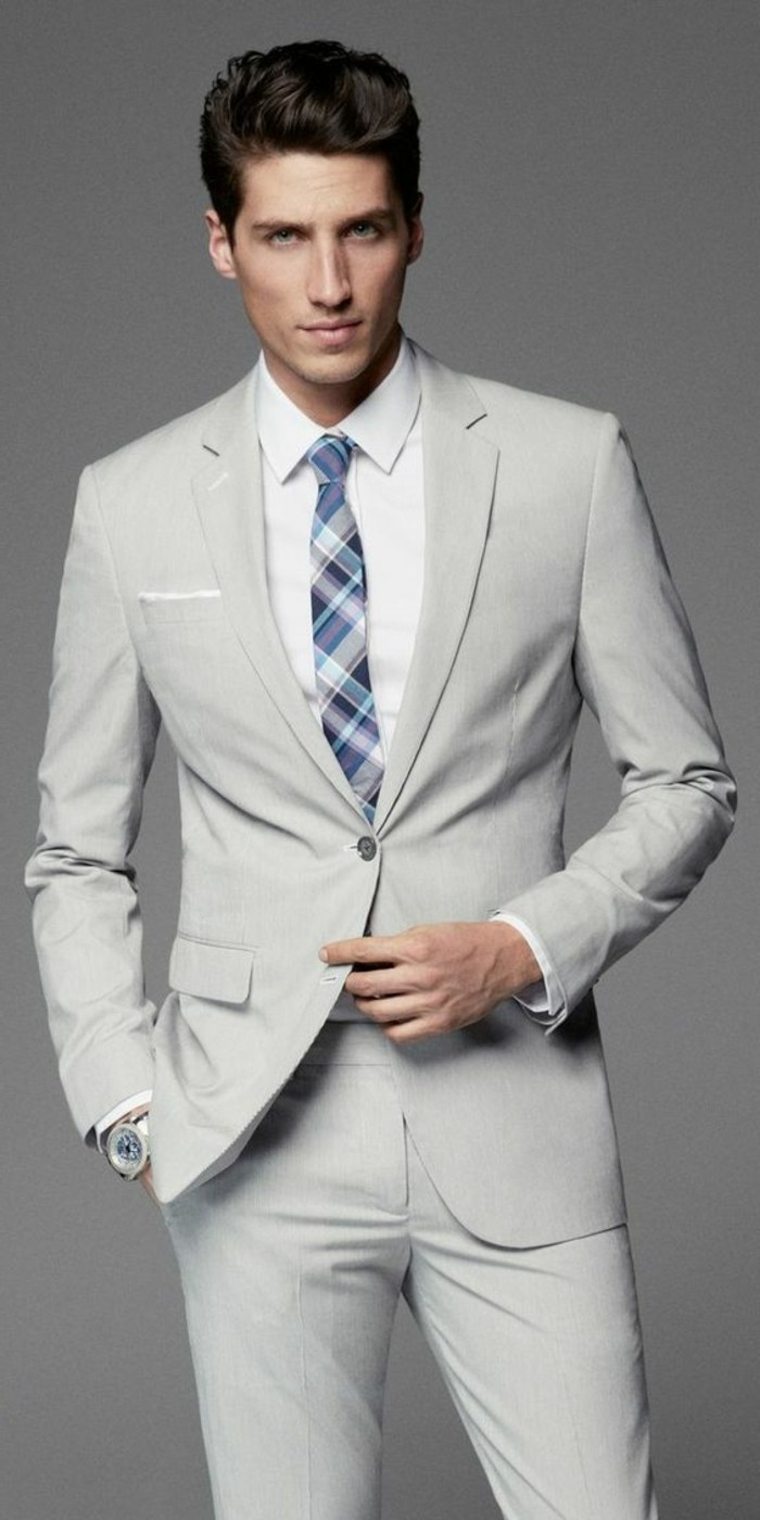 wristwatch and blue and white plaid tie, combined with a white shirt, and an off-white two piece suit, how to dress for a wedding male, young brunette man