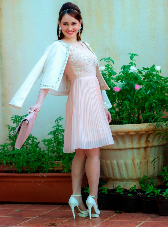 powder pink knee-length dress, with embroidered top, and pleated skirt, semi formal dress code, worn with white jacket, by smiling brunette woman