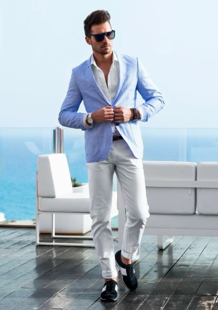 sports shoes in white and black, worn by brunette man with sunglasses, what is cocktail attire for men, dressed in white trousers, and a white shirt, buttoning a light blue blazer