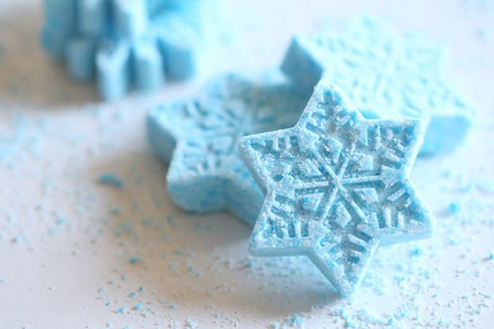 frosty pale blue bath fizzies, shaped like snowflakes, placed on a white surface, covered with light blue powder