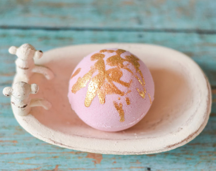 rose gold drizzle bath bomb, in light powdery pink, placed inside a pale pastel pink soap dish, bath fizzies recipes and ideas