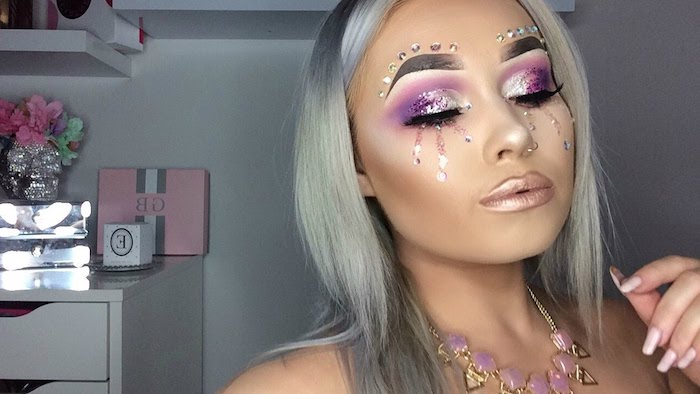 tears painted from pink glitter, decorating the face of a young woman, unicorn makeup, sparkly purple eyeshadow, pearly beige lipstick, large sharp eyebrows, and several silver pearl stickers on her forehead