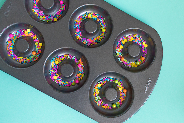 teflon dish in black, with donut-shaped moulds, containing multicolored sprinkles, bath bombs recipe ideas, pale blue background