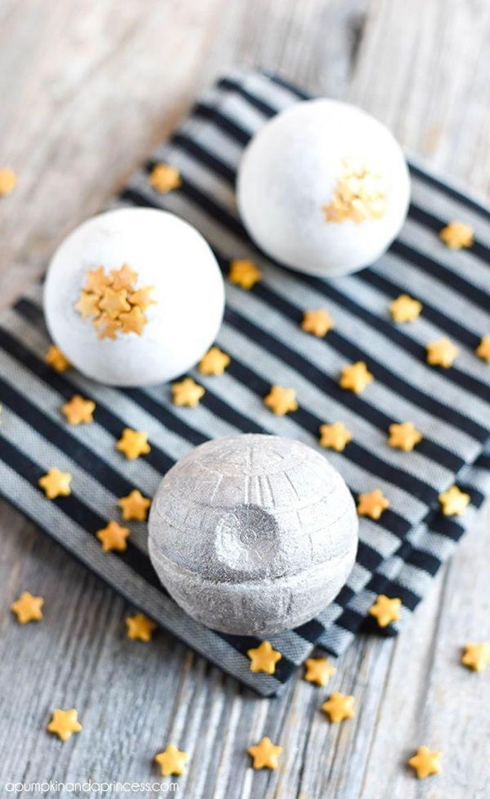 bath fizzies inspired by star wars, miniature pale gray death star, two white bath bombs, decorated with little yellow stars