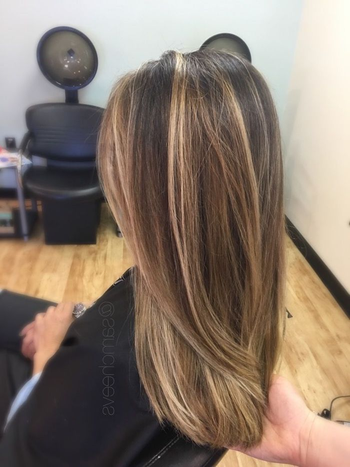hairdresser holding the tips of a woman's hair, brown and blonde hair, smooth and straightened, brunette with blonde highlights