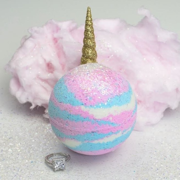 cotton candy in sparkly pale pink, behind a bath bomb in white, baby pink and blue, with silver glitter, and a unicorn horn, covered in golden glitter, a silver ring with large stone nearby