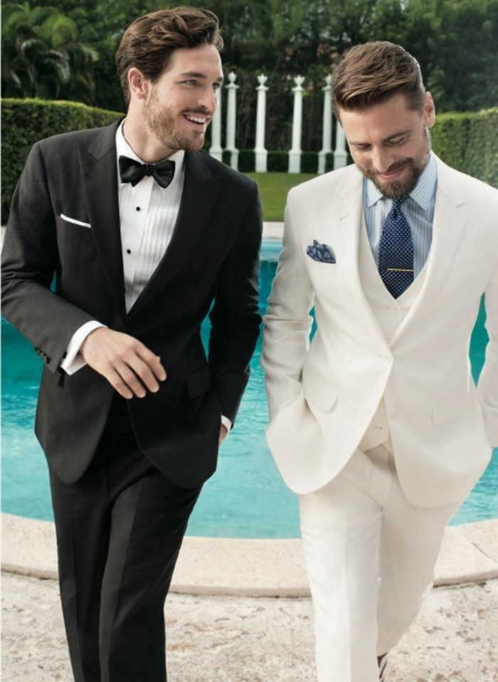 talking and smiling men, one wearing a black tuxedo, with white shirt and black bowtie, how to dress for a wedding male, the other in a white three piece suit, with light blue shirt, and dark blue tie