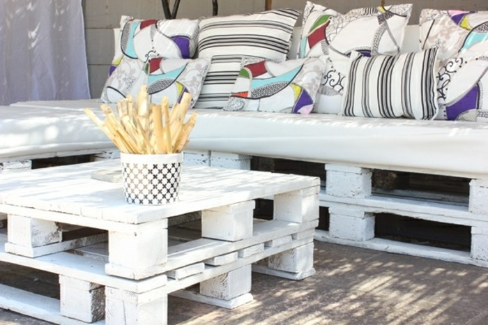 matching white pallet table, and corner sofa, pallet patio furniture, white cushions in different sizes, decorated with stripes, and colorful patterns