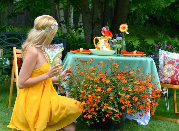 platinum blonde woman, with small flower crown, dressed in floaty, vibrant yellow strapless dress, admiring orange potted plants in a garden, while holding a glass of wine