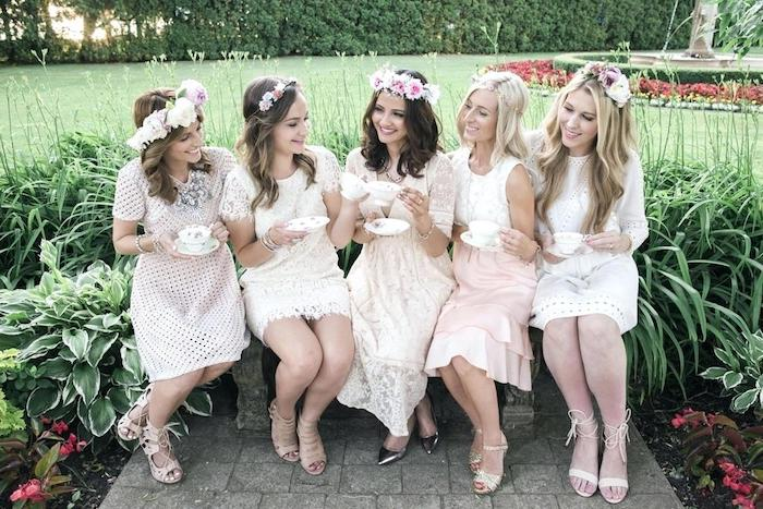 happy young women, sitting in a garden and having tea, all five are wearing pale pink and cream dresses, with ruffles and lace details, and flowers in their hair