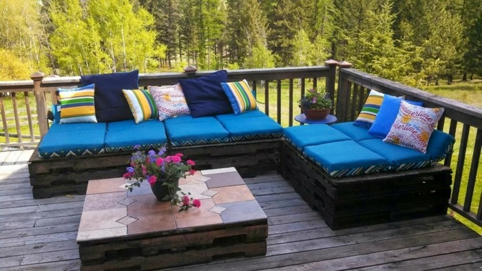 pallet patio furniture, set of two sofas made from wooden pallets, painted in dark brown, and covered with blue foam pillows, and multicolored cushions