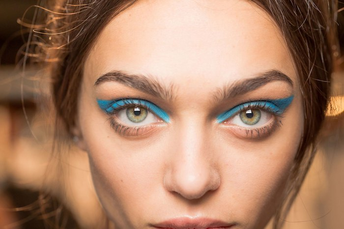 bushy eyebrows and green eyes, seen in close up, vivid teal blue eyeliner, and discrete nude lipstick, brunette hair tied back