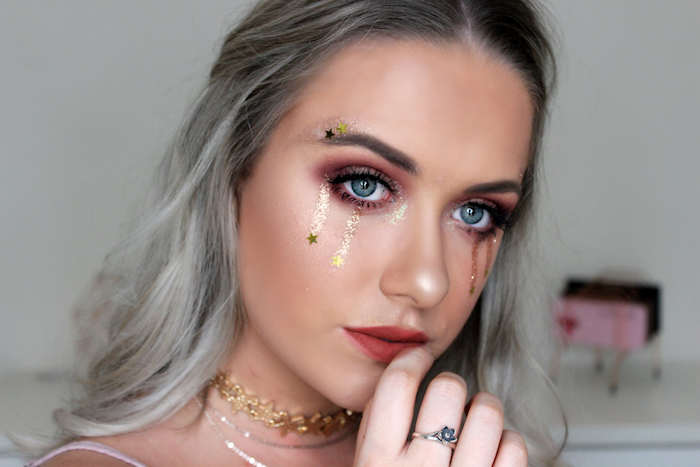 golden tears made from body glitter, with little star stickers, decorating the face of a woman, with maroon eye makeup, red lipstick and grey ombre hair