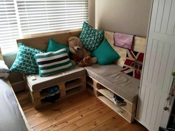 kids's room pallet couch, with a foam mattress, with a beige cover, decorated with several cushions, in turquoise and white, patterned and plain