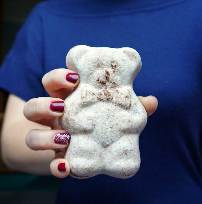 hand with dark red nail polish, holding a large beige bath bomb, shaped like a teddy-bear, funny bath balls ideas