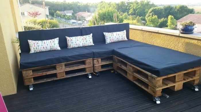 open space terrace, with black wooden flooring, and yellow walls, pallet patio furniture, corner sofa made from brown, wooden pallets on wheels, covered with black foam mattresses, and three cushions
