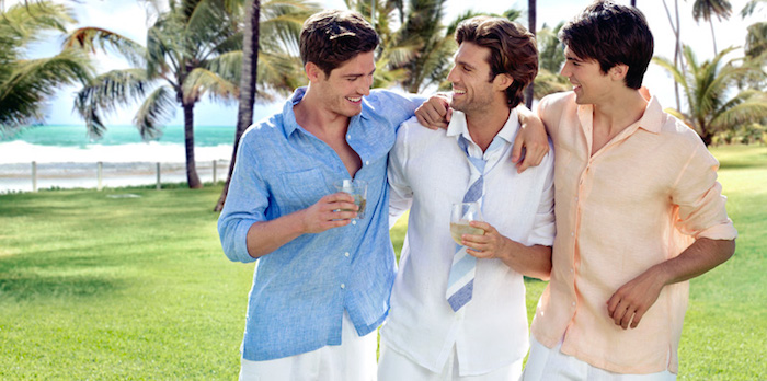men laughing on a green field near a beach, two of them are holding drinks, garden party attire, informal summer shirts in pale colors, white trousers and a necktie